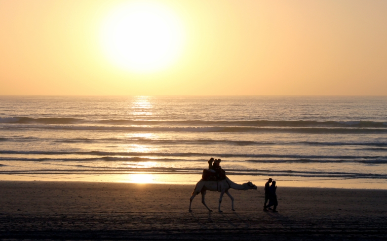 Camel riding on the beach .